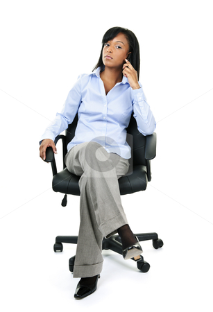 Businesswoman on phone sitting in office chair stock photo, Young confident black businesswoman on phone sitting in leather office chair by Elena Elisseeva
