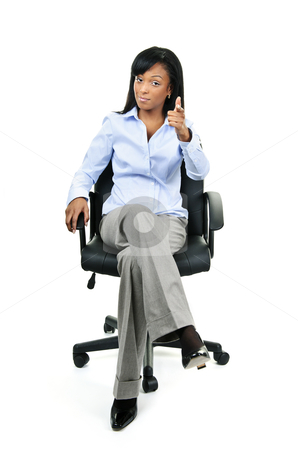 Businesswoman pointing sitting on office chair stock photo, Young confident black businesswoman sitting and pointing at camera by Elena Elisseeva