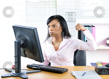 Angry black businesswoman at desk stock photo, Angry young black business woman punching computer in office by Elena Elisseeva