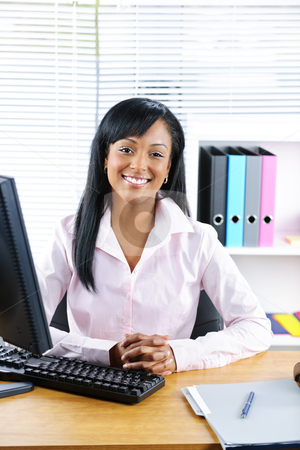 Smiling black businesswoman at desk stock photo, Smiling young black business woman at desk in office by Elena Elisseeva