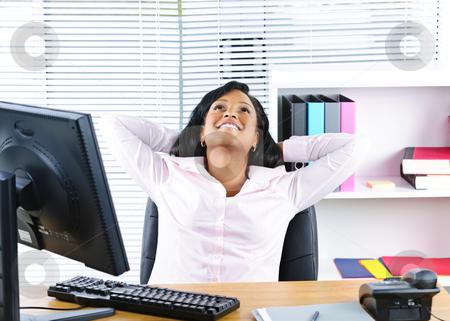 Black businesswoman resting at desk stock photo, Young black business woman resting at desk in office by Elena Elisseeva