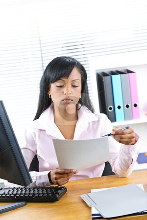 Black businesswoman working at desk stock photo, Young black business woman reading document at desk in office by Elena Elisseeva