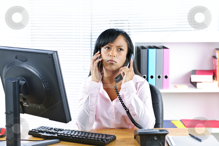 Black businesswoman using two phones at desk stock photo, Young black business woman multitasking using two phones in office by Elena Elisseeva