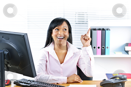 Businesswoman having idea at desk stock photo, Smiling black business woman pointing up with idea at desk in office by Elena Elisseeva