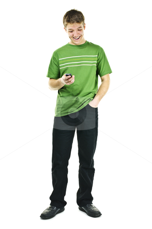 Smiling young man holding cell phone stock photo, Happy young man texting on cellphone standing full body isolated on white background by Elena Elisseeva