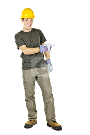 Smiling construction worker pointing to the side stock photo, Construction worker with hard hat pointing to the side isolated on white background by Elena Elisseeva