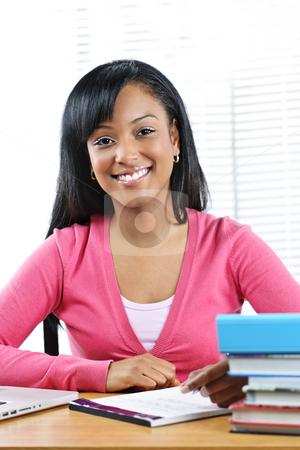 Female student studying stock photo, Smiling young black female student studying at desk by Elena Elisseeva