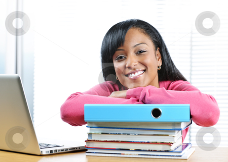 Female student studying stock photo, Smiling young black female student with textbooks at desk by Elena Elisseeva