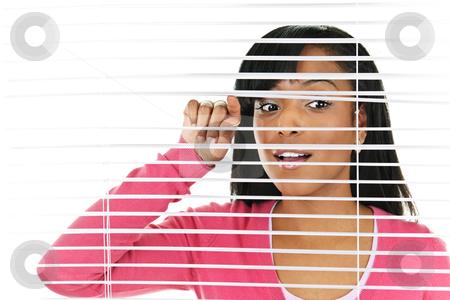 Woman looking through venetian blinds stock photo, Young black woman looking through horizontal venetian blinds by Elena Elisseeva