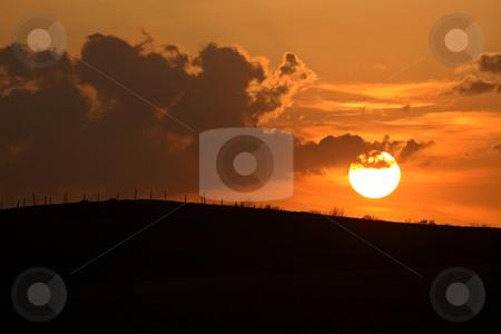 Sun setting behind a ridge in Saskatchewan stock photo, Sun setting behind a ridge in Saskatchewan by Mark Duffy