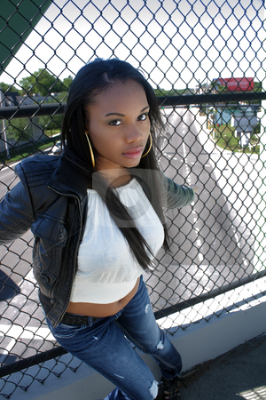 Beautiful Haitian Girl Outdoors (7) stock photo, A lovely young Haitian girl on a pedestrian overpass covered with chain-link fence, with the street visible below. by Carl Stewart