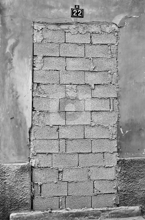 Bricked up door stock photo, Bricked up door and weathered wall of an abandoned building. Black and white. by sirylok