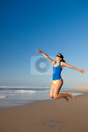 Jumping stock photo, Beautiful young woman jumping on the beach by ikostudio
