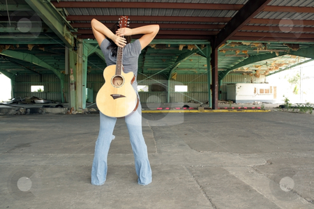 Beautiful Brunette with a Guitar (1) stock photo, A lovely young brunette wearing tattered jeans, stands with her back to the camera, holding a guitar at an abandoned warehouse facility. by Carl Stewart