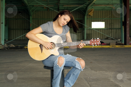 Beautiful Brunette with a Guitar (4) stock photo, A lovely young brunette wearing tattered jeans, sits with her guitar at an abandoned warehouse facility. by Carl Stewart