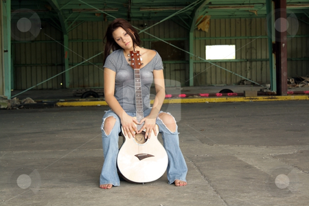 Beautiful Brunette with a Guitar (5) stock photo, A lovely young brunette wearing tattered jeans, sits with her guitar at an abandoned warehouse facility. by Carl Stewart
