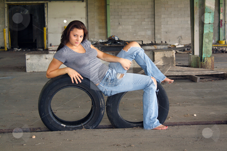 Sexy Brunette with Tattered Jeans (1) stock photo, A beautiful young brunette rests on two old tires at an abandoned warehouse facility. by Carl Stewart