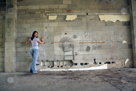 Sexy Brunette at a Block Wall (2) stock photo, A lovely young brunette wearing tattered jeans and a white T-shirt with black stripes, leans with her hands against an old, dilapidated block wall, looking back over her shoulder.  Wide shot with plenty of room for adding text, artwork, graffiti, etc. by Carl Stewart