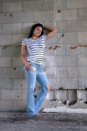 Sexy Brunette at a Block Wall (4) stock photo, A lovely young brunette wearing tattered jeans and a white T-shirt with black stripes, leans against an old, dilapidated block wall. by Carl Stewart