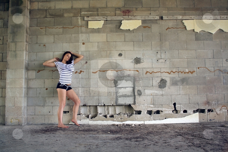 Sexy Brunette at a Block Wall (6) stock photo, A lovely young brunette wearing black boy shorts with white patterns and a white T-shirt with black stripes, stands facing the camera in front of an old, dilapidated block wall.  Wide shot with plenty of room for adding text, artwork, graffiti, etc. by Carl Stewart