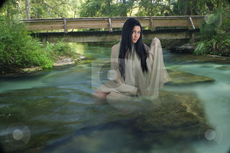 Beautiful Teen in a Creek stock photo, A lovely young teenage girl sits on a submerged rock, draped in sheer fabric, in a creek with crystal-clear flowing water. by Carl Stewart