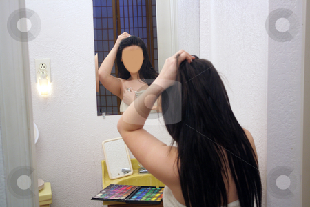 Identity Theft stock photo, A lovely teenage girl sits in front of her mirror without a face, preparing to make one with her palette of makeup. by Carl Stewart