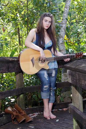 Beautiful Teen Girl with Guitar (4) stock photo, A lovely teenage girl stands, leaning on a wooden fence rail, with her acoustic guitar. by Carl Stewart