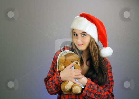 Teen Girl Santa's Helper (5) stock photo, A beautiful teenage girl wearing a Santa's helper hat and a comfy flannel nightgown, holds a sleepy teddy bear.  Plenty of room on frame left for inserting text, graphics, etc.  Textured background. by Carl Stewart
