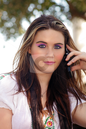 Beautiful Teen Girl with her Cell Phone (1) stock photo, Close-up of a lovely teenage girl talking on her cell phone outdoors, looking at the camera. by Carl Stewart