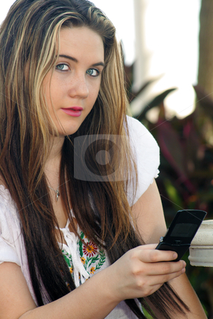 Beautiful Teen Girl Texting Outdoors stock photo, Close-up of a lovely teenage girl texting with her cell phone outdoors, looking at the camera. by Carl Stewart