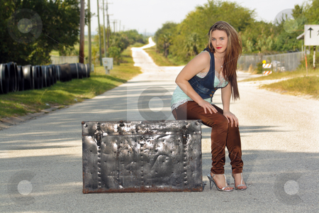 Teen Girl on a Trunk in the Street (4) stock photo, A lovely teenage girl sits fashionably on an antique trunk in the middle of a lonely country road. by Carl Stewart