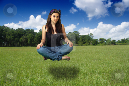 Teen Girl Sits Suspended Above a Grassy Field stock photo, A lovely teenage girl sits suspended above a grassy field. by Carl Stewart