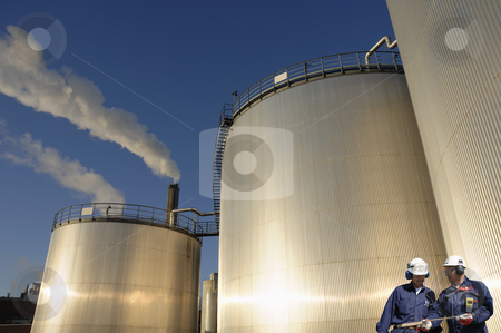 Engineers and fuel-storage tanks stock photo, two engineers, workers in front of giant industrial fuel-storage tanks by lagereek