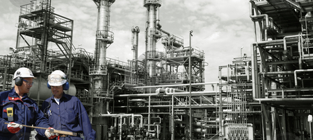 Oil workers and power industry stock photo, engineers, oil-workers with large oil and gas refinery in background, panoramic view by lagereek