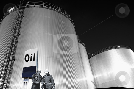 Oil-engineers and fuel-storage tanks stock photo, two oil-workers, engineers, with giant industrial fuel-tanks in background, commercial sign in foreground by lagereek