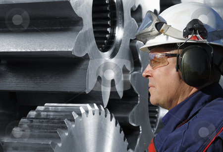 Mechanic with gears machinery stock photo, mechanic in profile, large steel power gear machinery in background by lagereek