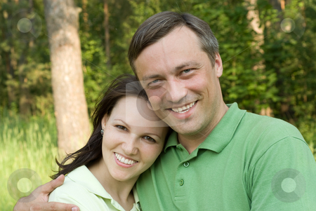 Happy couple in a park stock photo, happy couple in a summer park by Alevtina Guzova