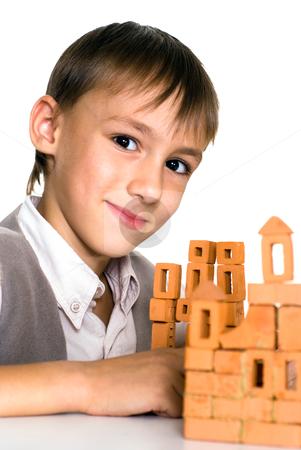 Handsome boy builds a toy castle  stock photo, handsome boy builds a toy castle on a white background by Alevtina Guzova