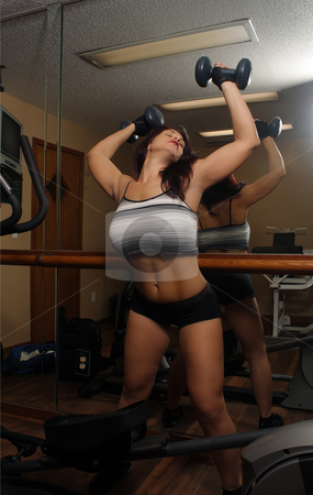 Lovely Athletic Female Working Out (3) stock photo, An attractive middle-age female works out with weights in a fitness facility with her back to the camera, facing a mirror. by Carl Stewart