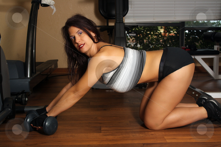 Lovely Athletic Female Working Out (4) stock photo, An attractive middle-age female works out with weights no the floor of a fitness facility. by Carl Stewart