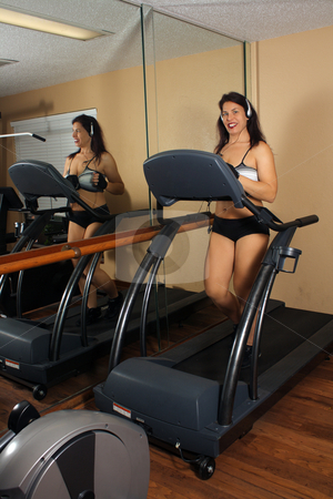Lovely Athletic Female Working Out (5) stock photo, An attractive middle-age female walks on a tread mill indoors. by Carl Stewart