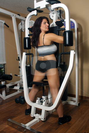 Lovely Athletic Female Working Out (7) stock photo, An attractive middle-age female works out on a weight machine. by Carl Stewart