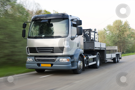 Truck on the road stock photo, Truck and trailer combination, carrying a forklift, driving at speed  by Corepics VOF