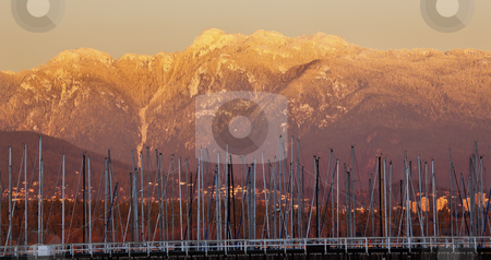 Vancouver Though Sailboat Masts Golden Snow Mountains Background stock photo, VancouverThrough Sailboat Masts From Jericho Beach Golden Snow Mountains Sunset British Columbia Pacific Northwest by William Perry