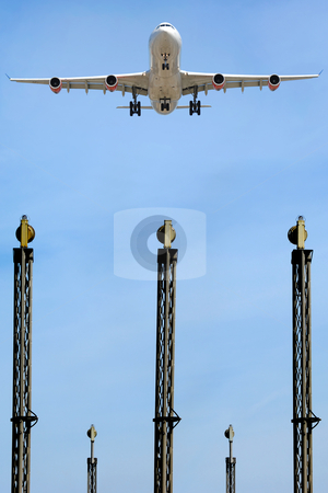 Plane over lights in airport stock photo, A plane is flying over the landing lights in an airport. by Lars Christensen