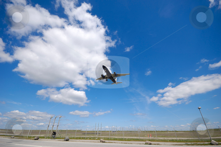 Low plane near airport stock photo, Plane is going to land. Blue and cloudy sky. by Lars Christensen
