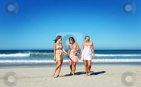 Three young woman having fun on the beach on a summer day stock photo, Three young woman having fun on the beach on a summer day by tish1