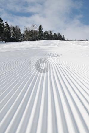 Tracks on ski slopes at beautiful sunny  winter day stock photo, tracks on ski slopes in snow at beautiful sunny  winter day with blue sky by Benis Arapovic