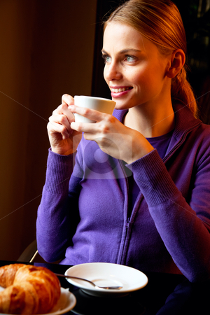 Young woman drinking cappuccino at breakfast stock photo, young woman drinking cappuccino at breakfast by ambrophoto