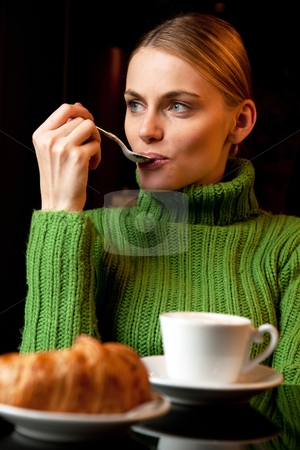 Young woman with a spoon in her mouth making breakfast with a cup of cappuccino and croissant stock photo, young woman with a spoon in her mouth making breakfast with a cup of cappuccino and croissant by ambrophoto